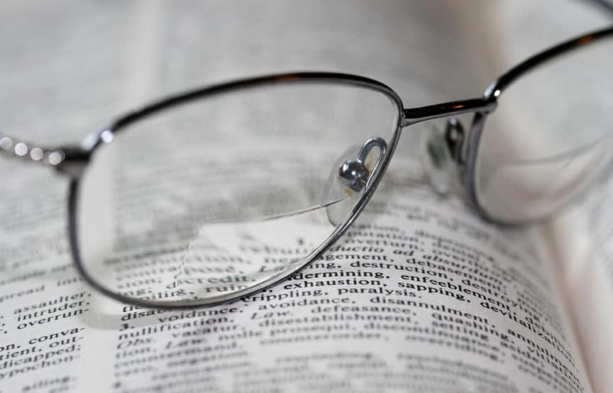 decision - Bifocal lenses in metal glasses resting on a book