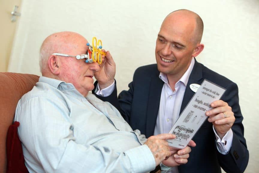 Optometrist Hugh Loughran tests a customer's eye in their own home