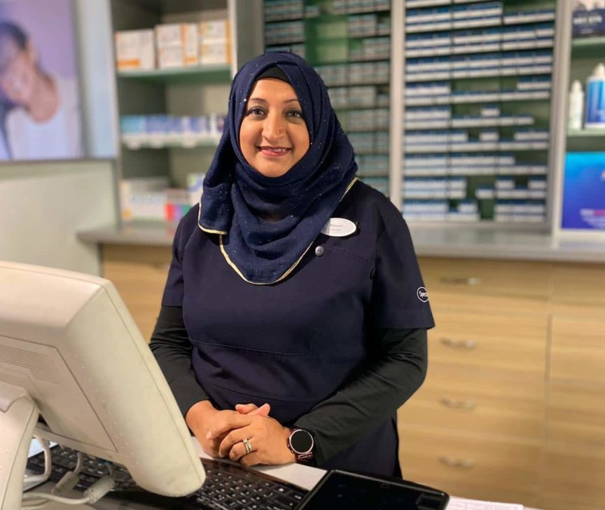 Woman in headscarf working in Specsavers shop