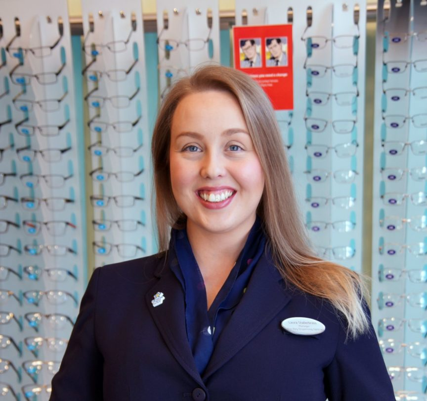 woman standing in Specsavers uniform in front of glasses for sale