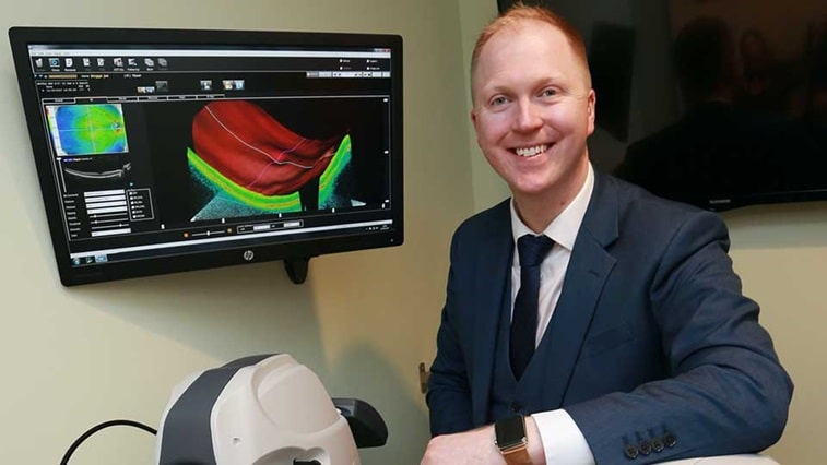 man in front of an OCT scan at Specsavers