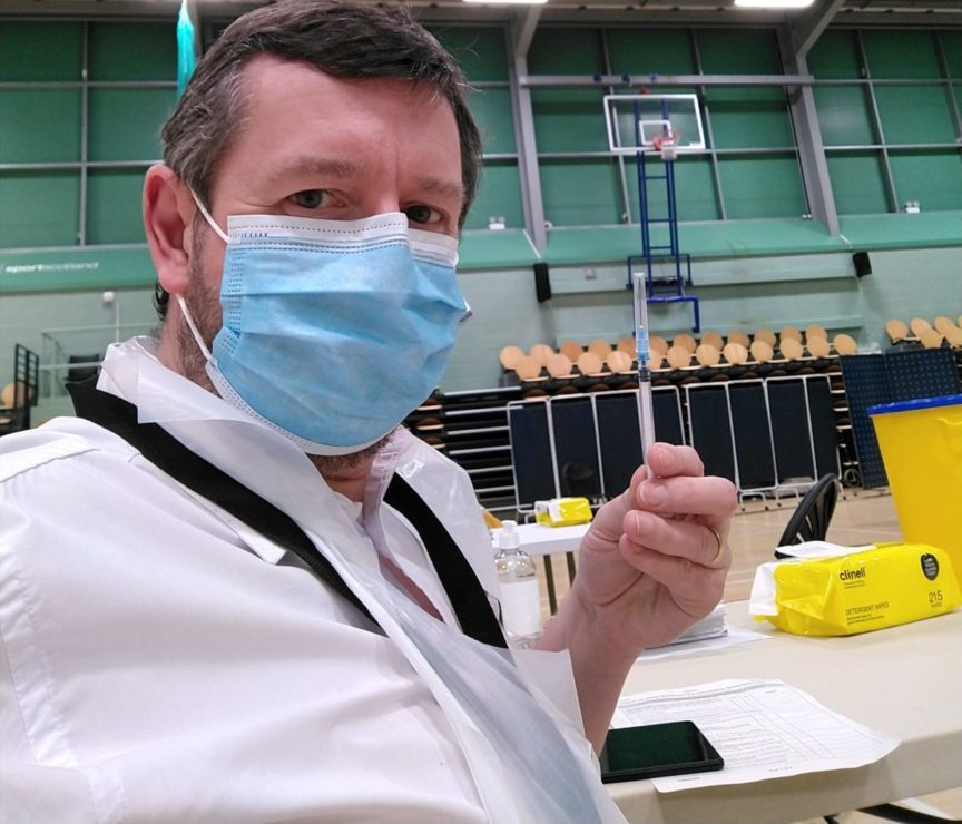 man in mask at vaccination centre