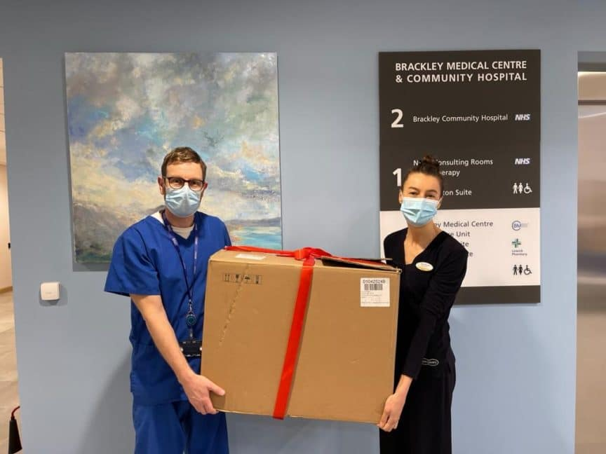man and woman holding large box in a hospital corridor
